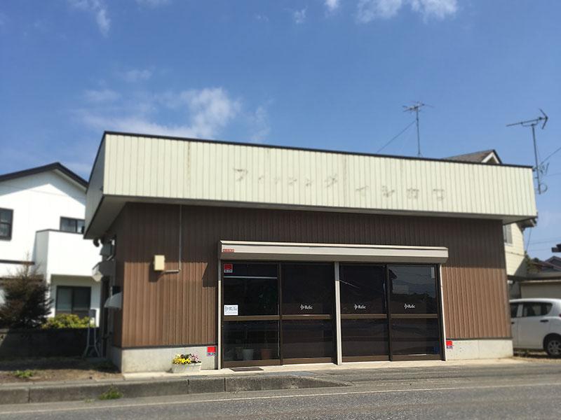 レリック スピーカー修理工房外観。鶴岡市稲生1-18-18。茶色い壁にクリーム色の屋根、ロールスクリーン にはレリック のロゴ。